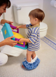 Mon handing little boy a potty seat in the bathroom