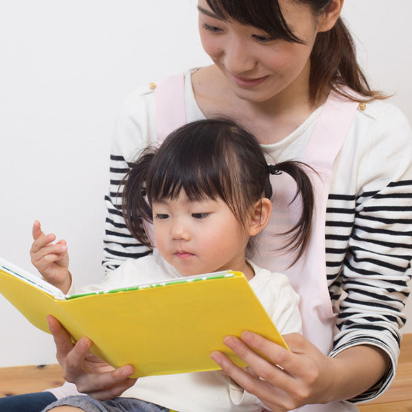 Woman reading a book to a young child