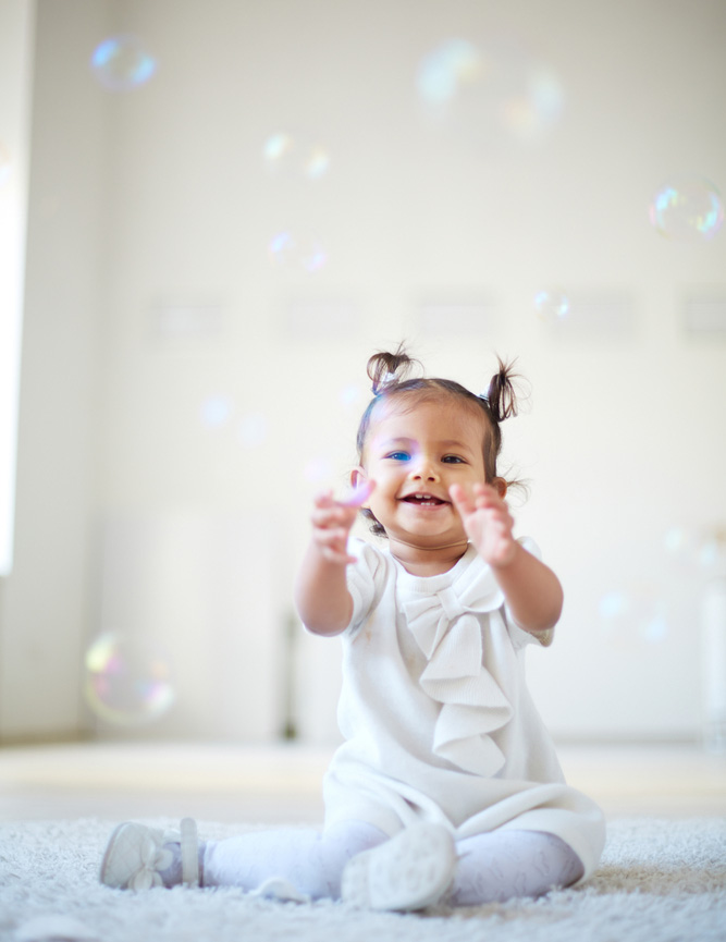 Laughing little girl surrounded by bubbles